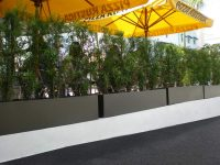 Line of gray rectangular planters lining a restaurant eating area
