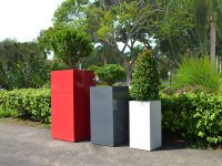 White, gray and red square planters lining a road