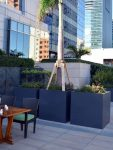 Three gray rectangular planters in an outdoor seating area